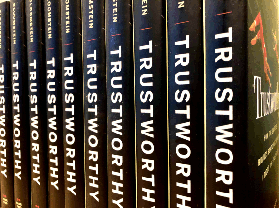 Trustworthy books stand lined up on a shelf.
